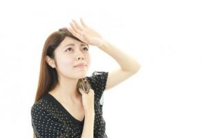 汗をハンカチで拭く女性