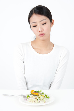 attractive asian woman eating salad