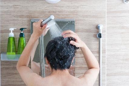 シャワーで頭をすすぐ男性