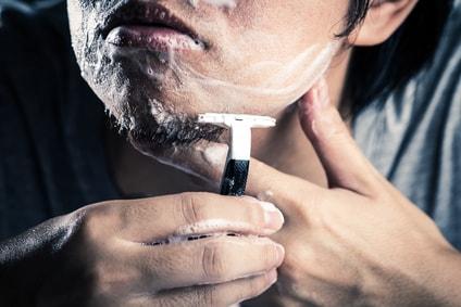 カミソリで髭を剃る男性