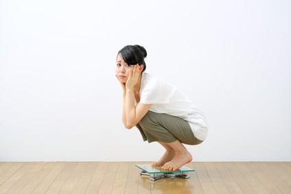 体重計に乗って悲しい顔をしている女性