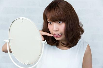 鏡で舌を確認する女性