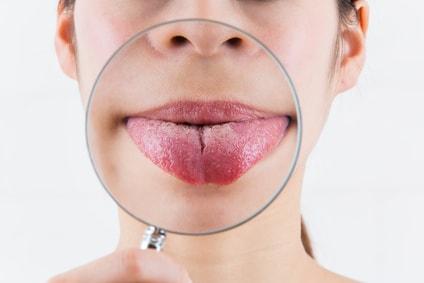 舌を出して虫眼鏡をあてる女性