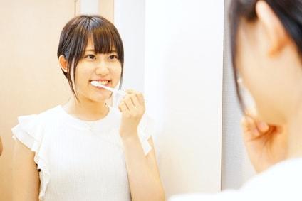 鏡を見ながら歯磨きをする女性
